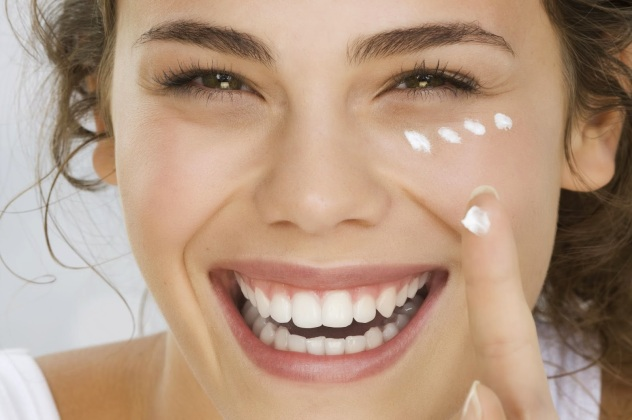 6967765Young-woman-putting-cream-on-face-smiling-2-1798614
